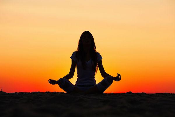 Full shot a contraluz de chica meditanto ante puesta de sol